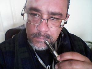 El autor luce encabronadamente guapo mientras aspira su pipa de vapor enfundado en la bata que le obsequió el mismísimo Mauricio Garcés.